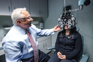 Sid Savitt O.D. using vision exam equipment