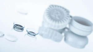contact lenses on glass table in front of open case